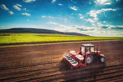 Bauer bringt das Saatgut aus auf dem Feld mit dem Traktor